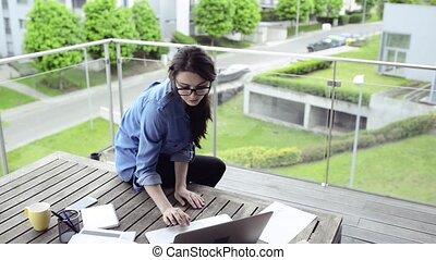 Beautiful woman on balcony working from home. - Beautiful...