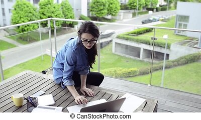 Beautiful woman on balcony working from home.
