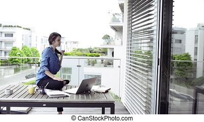 Beautiful woman on balcony working from home. - Beautiful...