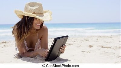 Beautiful woman on beach wearing straw hat works on her...