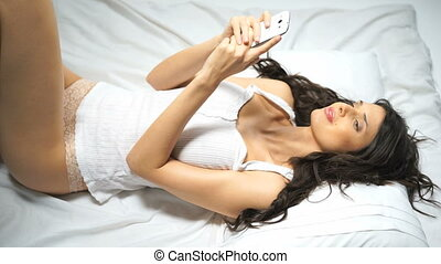 Beautiful woman on bed - Beautiful young brunette woman in...