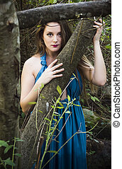 Beautiful woman on forest with an evening dress