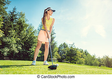 Beautiful woman on golf course at tee