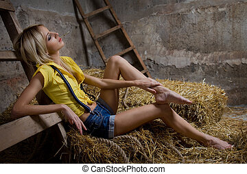 Beautiful woman on hay - Beautiful blond woman lying down on...