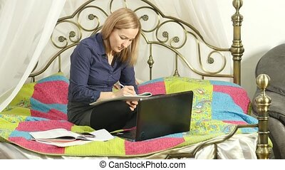 beautiful woman on-line education in home. Student on a bed with workbook and laptop. 4K