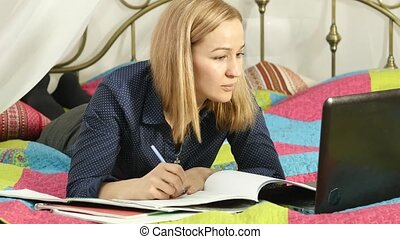 beautiful woman on-line education in home. Student on a bed with workbook and laptop.