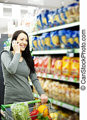 Beautiful woman on mobile phone at supermarket