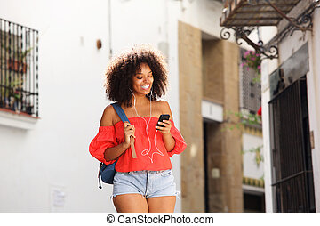 Beautiful woman on street with headphones and smart phone
