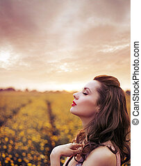 Beautiful woman on summer flower meadow