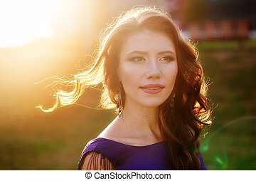 beautiful woman on the background of the setting sun