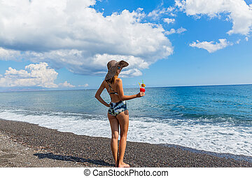 Beautiful woman on the beach with a cocktail