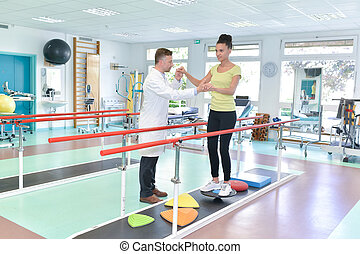 beautiful woman on treadmill rehabilitation helped by therapist