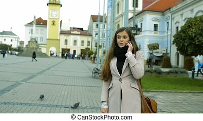 Beautiful woman outdoors in old town making phone call
