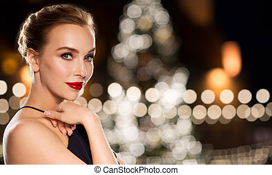 beautiful woman over christmas tree lights