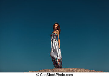 Beautiful woman over the blue sky