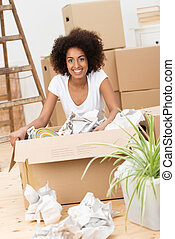 Beautiful African American woman packing to move house sitting on the hardwood floor in front of a brown cardboard carton surrounded by crumpled paper