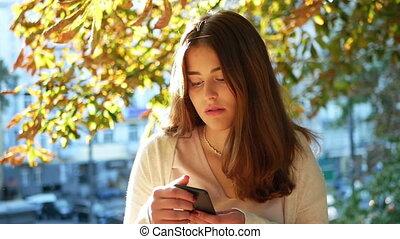 Beautiful woman park smartphone - Beautiful woman stands...