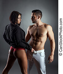 Beautiful woman passionately looks at muscular man