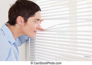 Beautiful woman peeking out a window