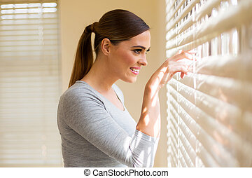 woman peeking through window blinds - beautiful woman ...