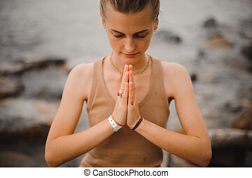 beautiful woman performing namaste gesture with closed eyes