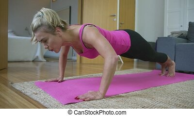 Beautiful woman performing push-ups - Lovely blonde woman in...