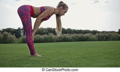 Beautiful woman performing the Down Dog yoga pose in the park. Sporty blond young woman with pony tail working out outdoors barefoot on green grass, standing downward facing dog posture, full length