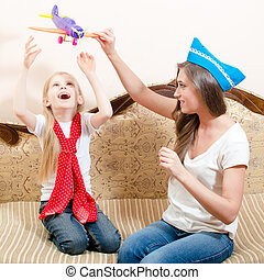 Beautiful woman playing airplane with child girl, having fun, happy smiling sitting on sofa