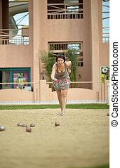 Beautiful  woman playing Boules game
