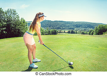 Beautiful woman playing golf on open course