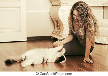Beautiful woman playing with a cat at apartment