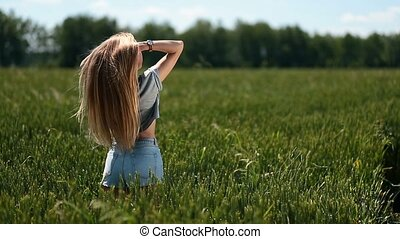 Beautiful woman playing with hair in the wind