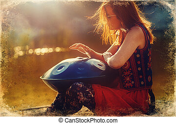 beautiful woman playing with hangdrum in nature. Old photo ...