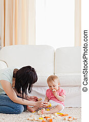 Beautiful woman playing with her baby in while sitting on a carpet in the living room