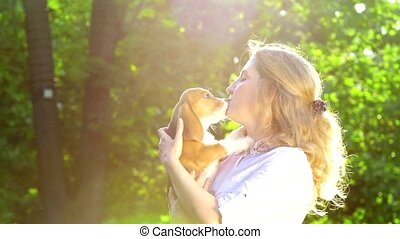 beautiful woman playing with her beagle dog in park. Slow motion