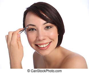 Happy smile from beautiful young caucasian woman using tweezers to pluck her eyebrow as part of make up routine. Taken against a white background.