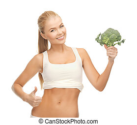 woman pointing at her abs and holding broccoli