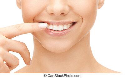 beautiful woman pointing to teeth