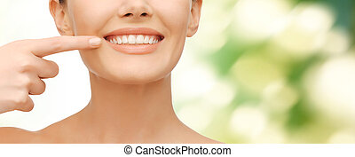 beautiful woman pointing to teeth - beauty and dental health...