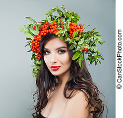 Beautiful woman portrait. Brunette female model with healthy curly hairstyle, makeup and red berries and green leaves wreath