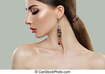 Beautiful woman portrait, profile. Female model with makeup and fashion jewelry earring