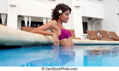 beautiful woman poses in a swimming pool. shot with the...