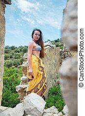 Beautiful woman posing among antique ruins