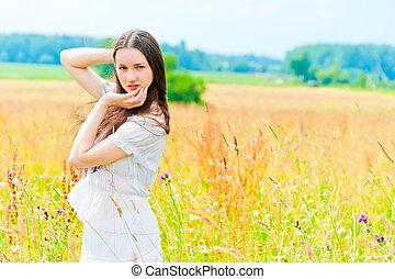 beautiful woman posing in a field of flowers