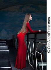 Beautiful woman posing in red long dress