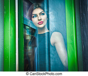 Beautiful woman posing in window