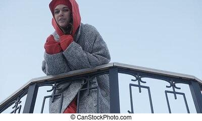 Beautiful woman posing nearrailing