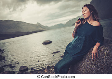 Beautiful woman posing on the shore of a wild lake, with mountains on the background.