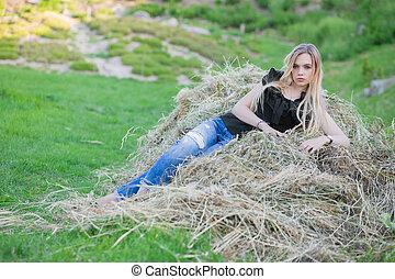 Beautiful woman posing sitting on the hay.