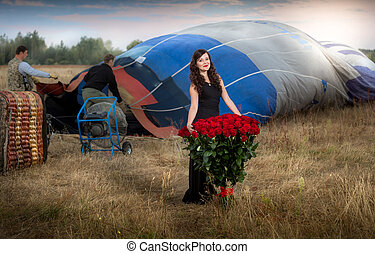Beautiful woman posing with bunch of roses at hot air balloon